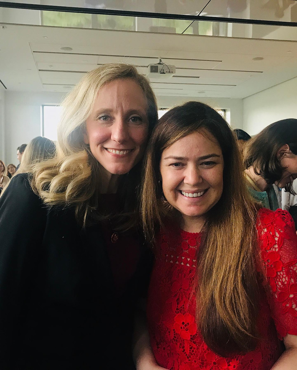 Kristin and Congresswoman Spanberger stand side by side with smiles on their faces. Kristin is wearing a red lace shirt and the Congresswoman has on a black blazer.