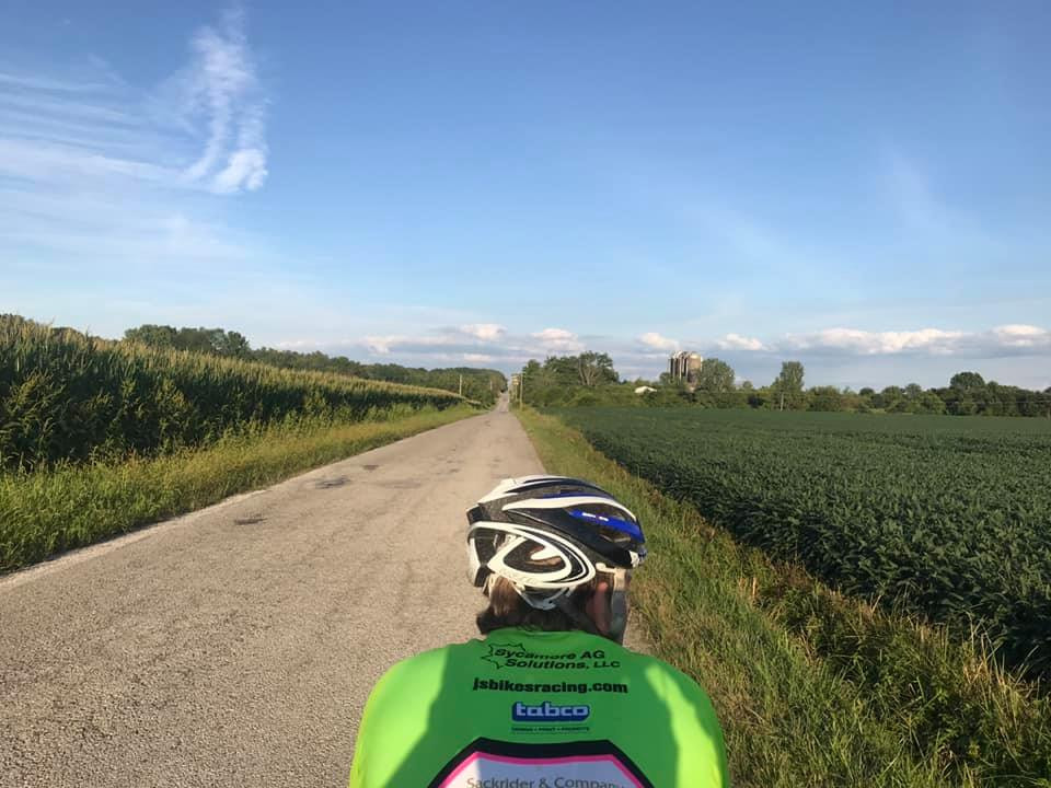 PD: The back of a cyclist piloting a tandem bike down a country road with a few rolling hills ahead. There are large corn stalks on the left side of the road and soybeans on the right. There are 4 silos in the distance and the top of a white barn. The sky is blue with white wispy clouds.