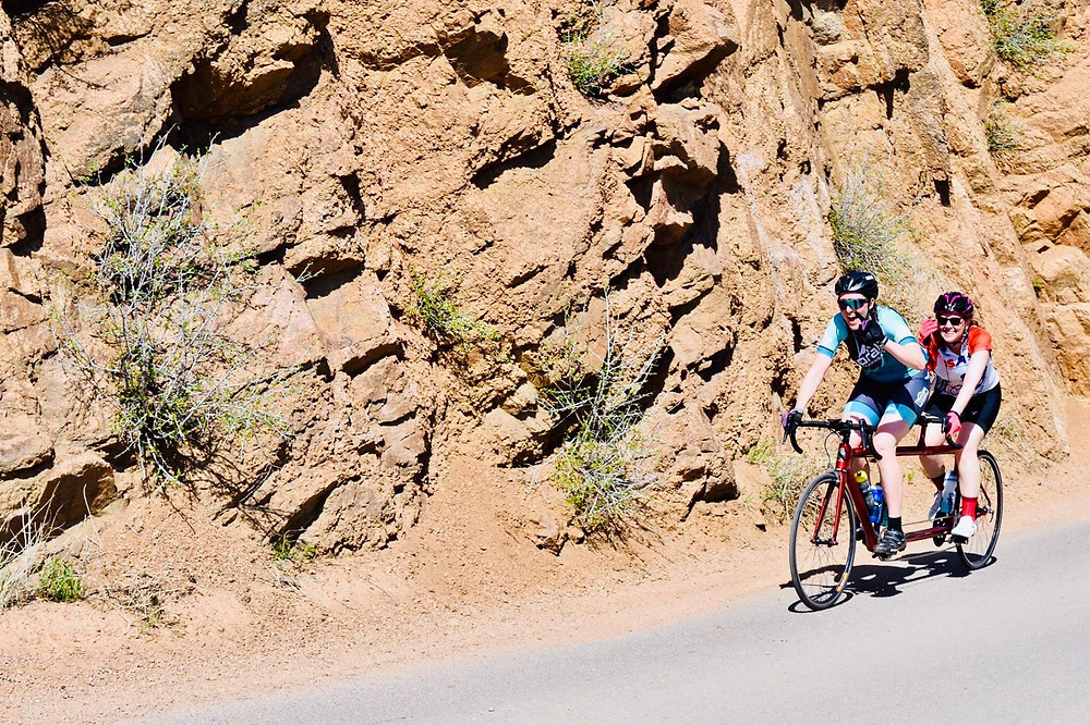 PD: Kristin and Ash climbing Gold Camp Road. They are both smiling and it is very sunny.