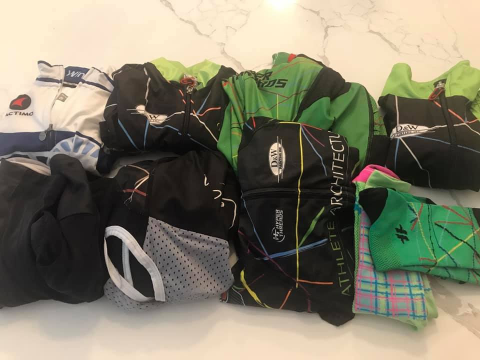 PD: A pile of different cycling outfits folded side by side. They are mostly black with bright green and other colors. There are two pairs of bright green matching socks.