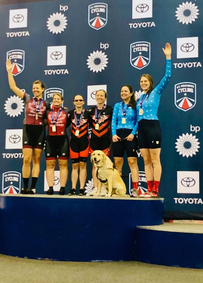 PD: Kristin, Zoe and Ash stand on the podium at the U.S. Para Cycling Track Open. Kristin and Zoe are wearing blue cycling suits with black shorts, and Ash has her left arm raised. Four other cyclists are also standing on the podium with them, and everyone has their arms around each other.