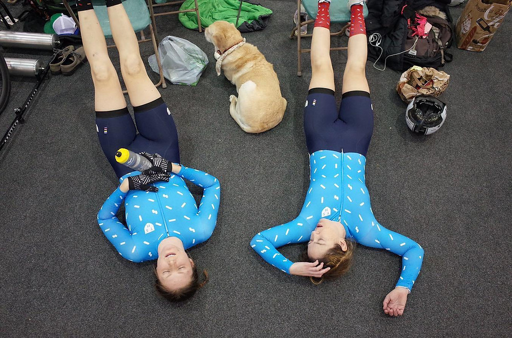 PD: Kristin and Ash are lying next to each other, flat on the floor with their legs propped up on green chairs. They look absolutely exhausted after their race! You can see Zoe resting on the floor in between the two of them.
