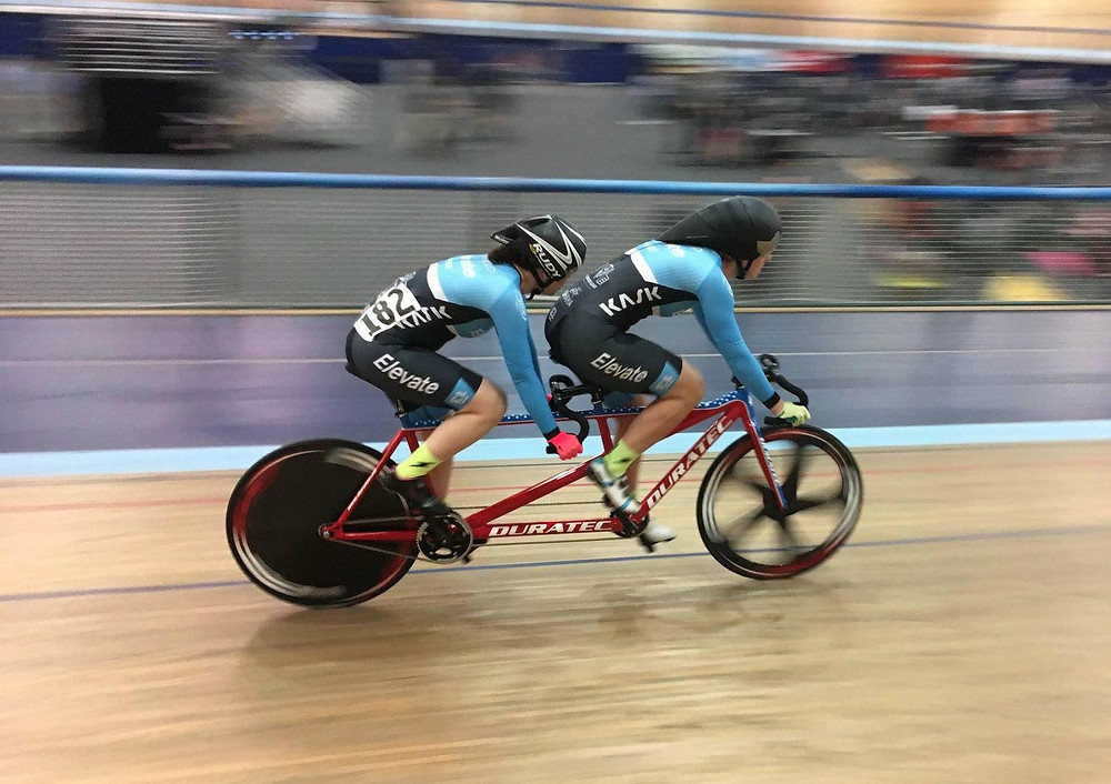 Kristin and her pilot Liesel riding their red Duratec tandem bicycle on the indoor Velodrome Track in Carson, CA. They are both wearing matching light blue cycling kits and black helmets. The background and the bike's wheels are blurred because the bike is in motion.