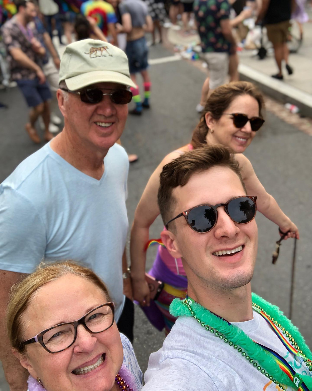 Brother Tim, Mom, Dad, and Kristin all smiling during a selfie at the Pride Parade.