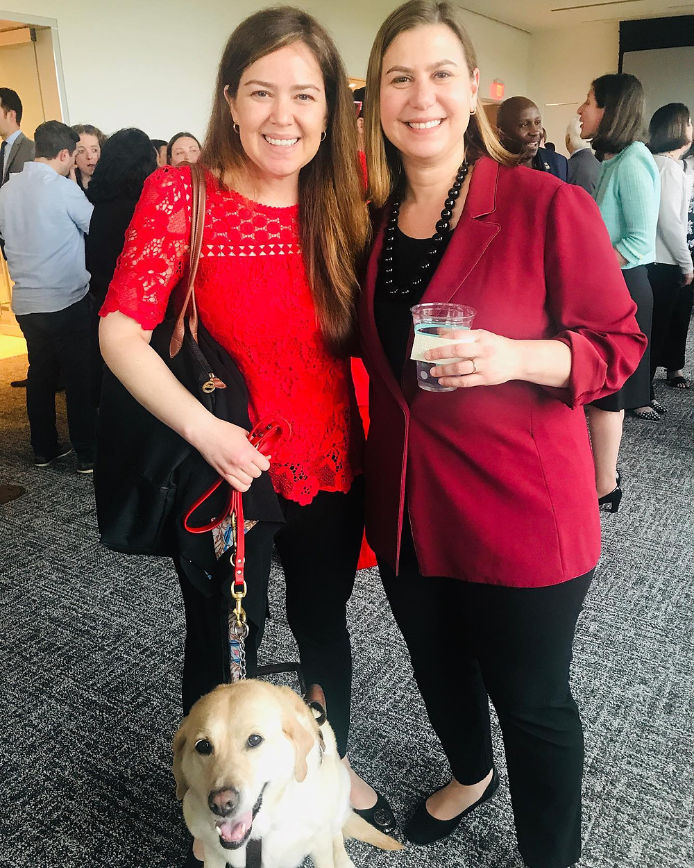 Kristin wears a red lace top and black pants and stands next Congresswoman Slotkin who is wearing a red blazer and black pants. They are both smiling and the Congresswoman is holding a glass in her hand. Kristin is holding Zoe on a red leash and Zoe is sitting on the floor in front of them with a big smile on her face.