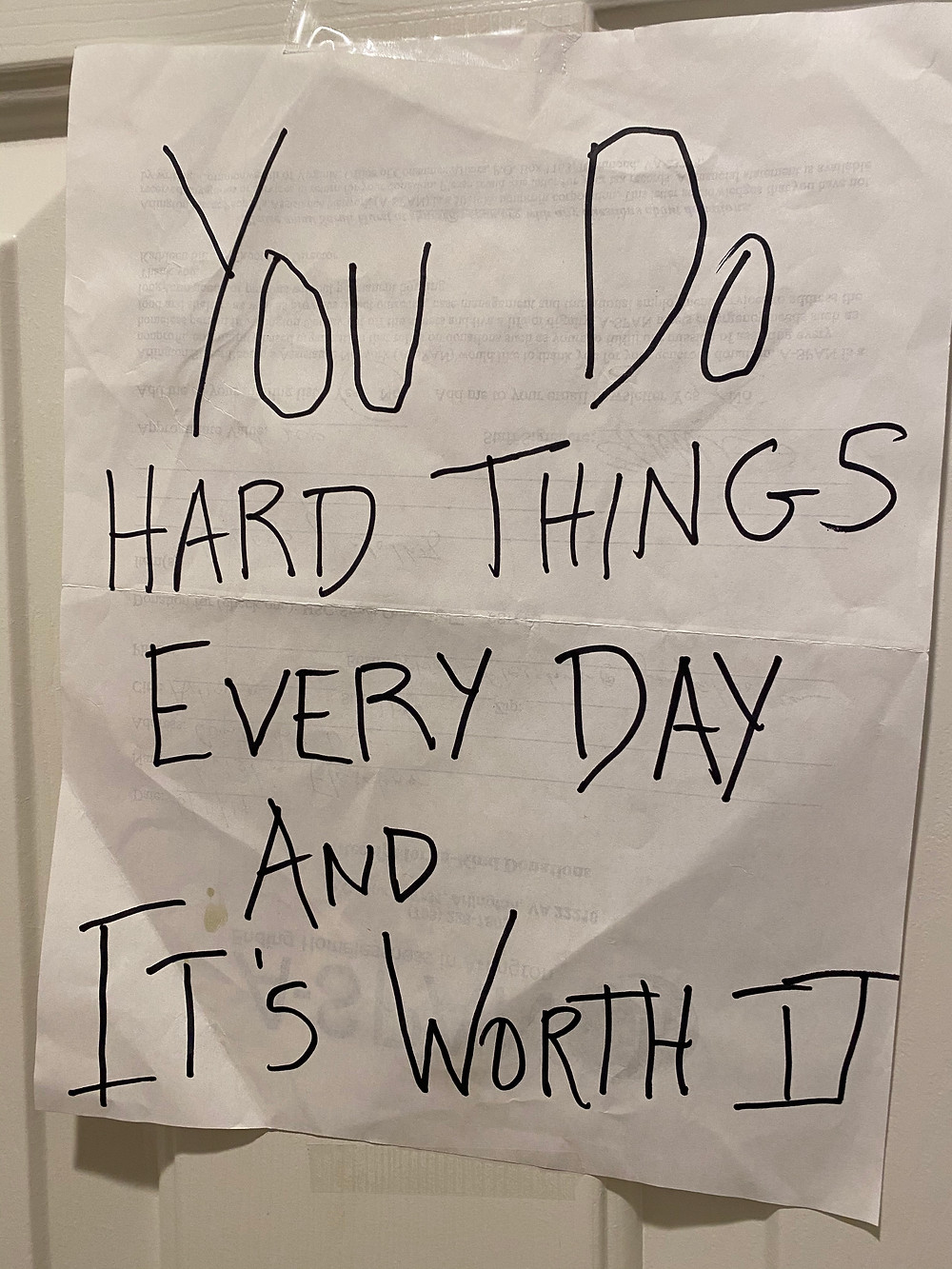 """PD: A piece of paper taped to a door. Handwritten on the paper in black pen is the phrase: """"You do hard things every day and it's worth it"""""""