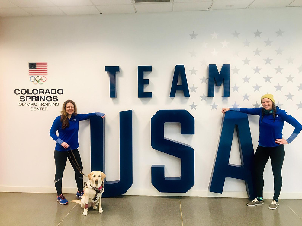 PD: Kristin, Zoe and Ash (Kristin's Bike Pilot at camp) stand in front of giant blue letters spelling out TEAM USA at the Colorado Spring Olympic Training Center. Kristin and Ash are both smiling, wearing matching blue pullovers. Zoe looks serious and is wearing a leopard print bandana.