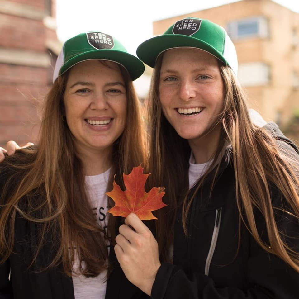"""PD: Kristin and Ash stand together on the campus of University of Illinois wearing matching green and white @tenspeedhero hats and black jackets. They are smiling, and Ash is holding up an orange-reddish leaf."""""""