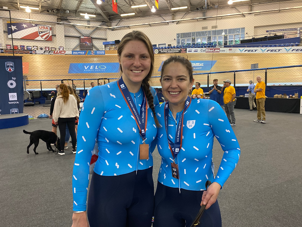 PD: Ash and Kristin at the Para Cycling Track Open. They are both smiling big and have their arms around each other. Around their necks are medals!