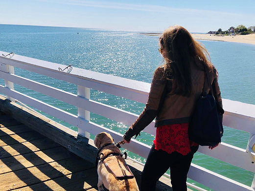 Zoe leads Kristin on a boardwalk. The water is bright blue and the sun shines brightly on it.