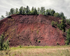 "Chris Mortenson ""Overburden""  The Mesabi Range in Minnesota is a geographical area that spans 110 miles from the towns of Grand Rapids to Babbitt. Subterrainly noted by an elongate trend of cherty Precambrian iron-rich deposit, The Range produces seventy-five percent of the iron ore in the United States. There are currently six mines producing ore and many that have been exhausted or abandoned along the expanse. The ore is removed through open- pit mining leaving vast and deep scars on the landscape, but the unusable soil - known as overburden - which is removed to get to the iron-rich deposits below is piled into small mountains along The Range, leaving the geographic area in a constant state of topographic flux. Tumulus is a visual investigation of this human-altered landscape, but it is also a document of the cultural and societal complexities of The Range. It is an area that is largely dependent on the economical might of the mining industry, yet subject to market booms and busts. As the country has moved further away from a manufacturing-based economy, The Range has seen its own economic hardships. These hardships ebb and flow with the market and the political gamesmanship of the present terrif wars."