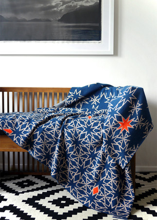 Knitted lambswool blanket in diesel and dusty peach with neon orange highlights. This blanket features a bespoke pattern designed using the initials A and M. Knitted using the double bed jacquard technique for a float free striped reverse with hand embroidered neon accents.