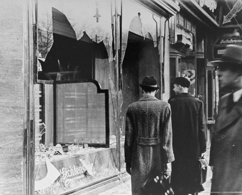 Germans pass by the broken shop window of a Jewish-owned business that was destroyed during Kristallnacht
