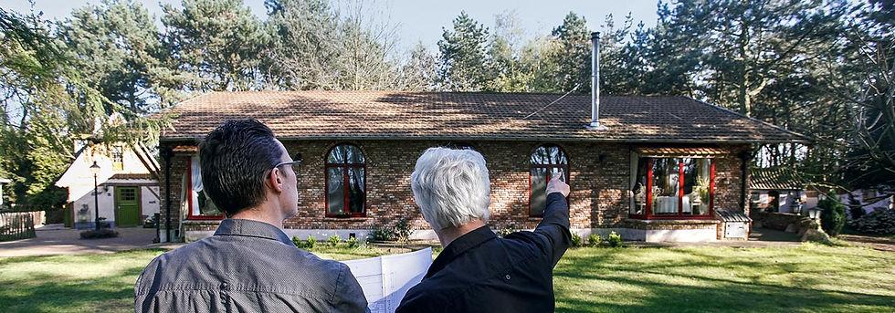 Vader en zoon dakwerkers met architectenplan in de hand aan de voorzijde van een woning.
