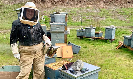 Beekeeper Siobhan wearing a fringe leather jacket to inspect her bees.  There are numerous beehives in the background.