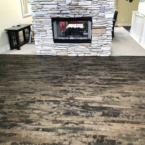 Refinished maple wood floors with ebony finish in front of a fireplace