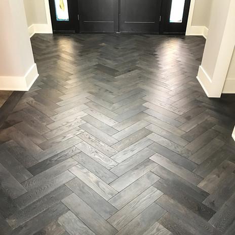 Installed maple wood floors with ebony finish in a herringbone pattern
