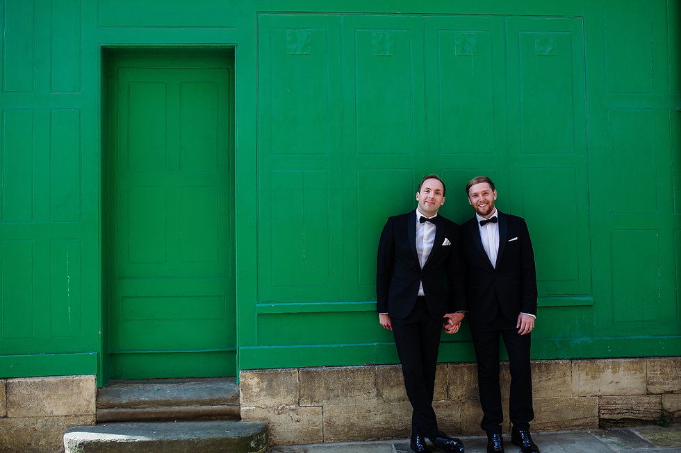Two grooms in front of a green wall in Oxford after getting married
