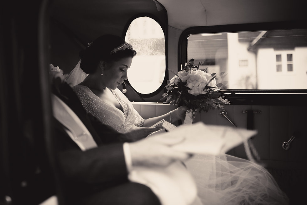Bride in wedding car with flowers texting husband to be black and white