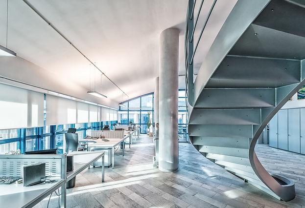 Grossraumbüro mit Wendeltreppe und Betonsäulen