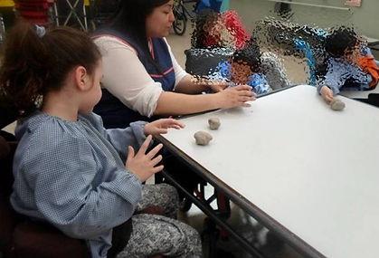 Situación escolar con niños y docentes, alrededor de una mesa que genera barreras de acceso a una niña con discapacidad motora
