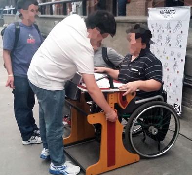Muchacho probando la mesa con otro muchacho que está regulando la altura