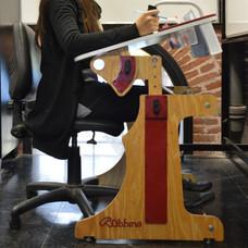 Muchacha sentada usando la Niña en escuela escribiendo y sujetándose desde la manija en la Mesa Inclusiva Robbina en posición inclinada