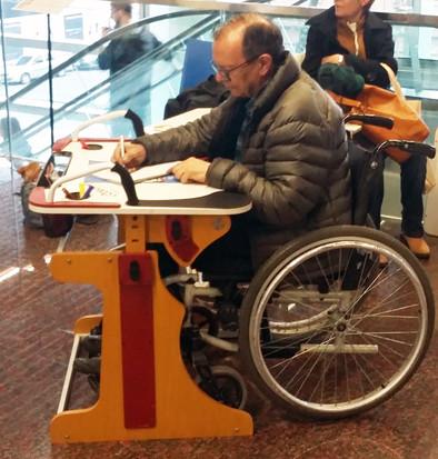 Adulto escribiendo en la Mesa Inclusiva Robbina