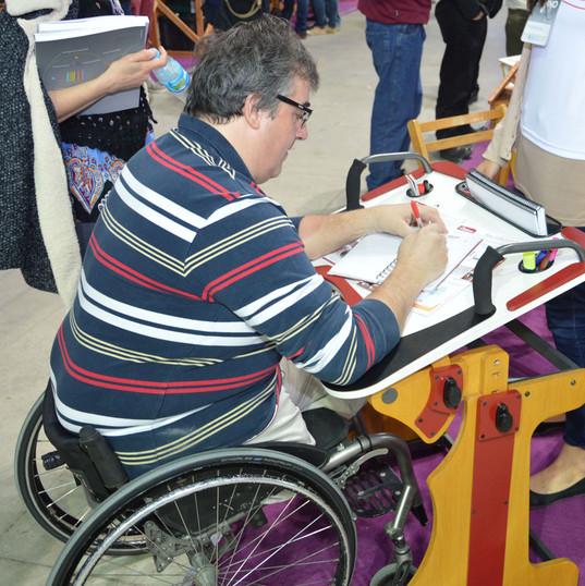 Muchacho escribiendo en la Niña en escuela escribiendo y sujetándose desde la manija en la Mesa Inclusiva Robbina en el Concurso Innovar