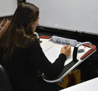 Muchacha escribiendo sobre la Mesa Inclusiva Robbina