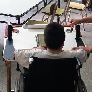 Niño de espalda usando la Mesa Inclusiva Robbina