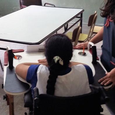 Niña de espalda, en escuela usando la Mesa Inclusiva Robbina