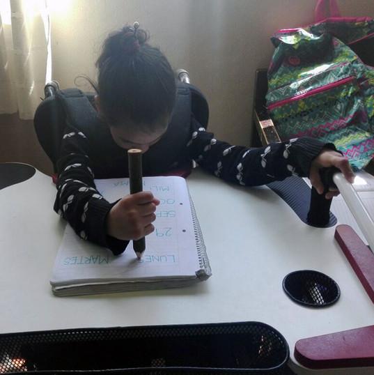 Niña en escuela escribiendo y sujetándose desde la manija en la Mesa Inclusiva Robbina