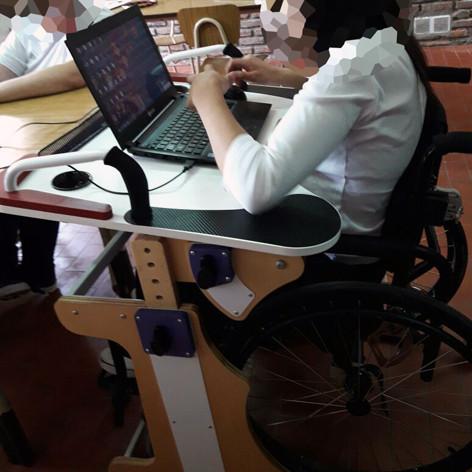 Chica en escuela utilizando la notebook sobre la Mesa Inclusiva Robbina