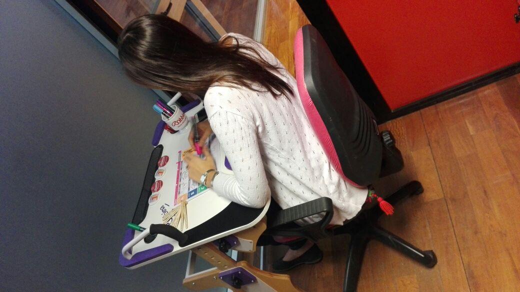 Muchacha de espalda escribiendo sobre la Mesa Inclusiva Robbina