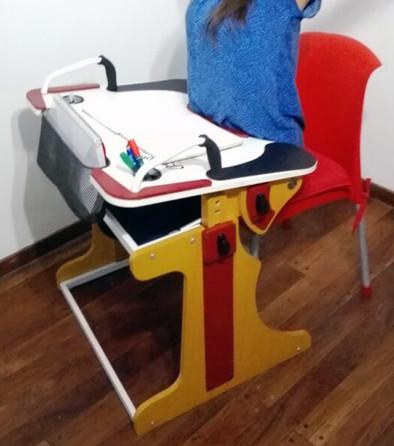 Muchacha sentada en una silla y utilizando la Niña en escuela escribiendo y sujetándose desde la manija en la Mesa Inclusiva Robbina