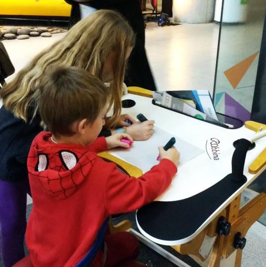 Niño y niña dibujando sobre la Mesa Inclusiva Robbina