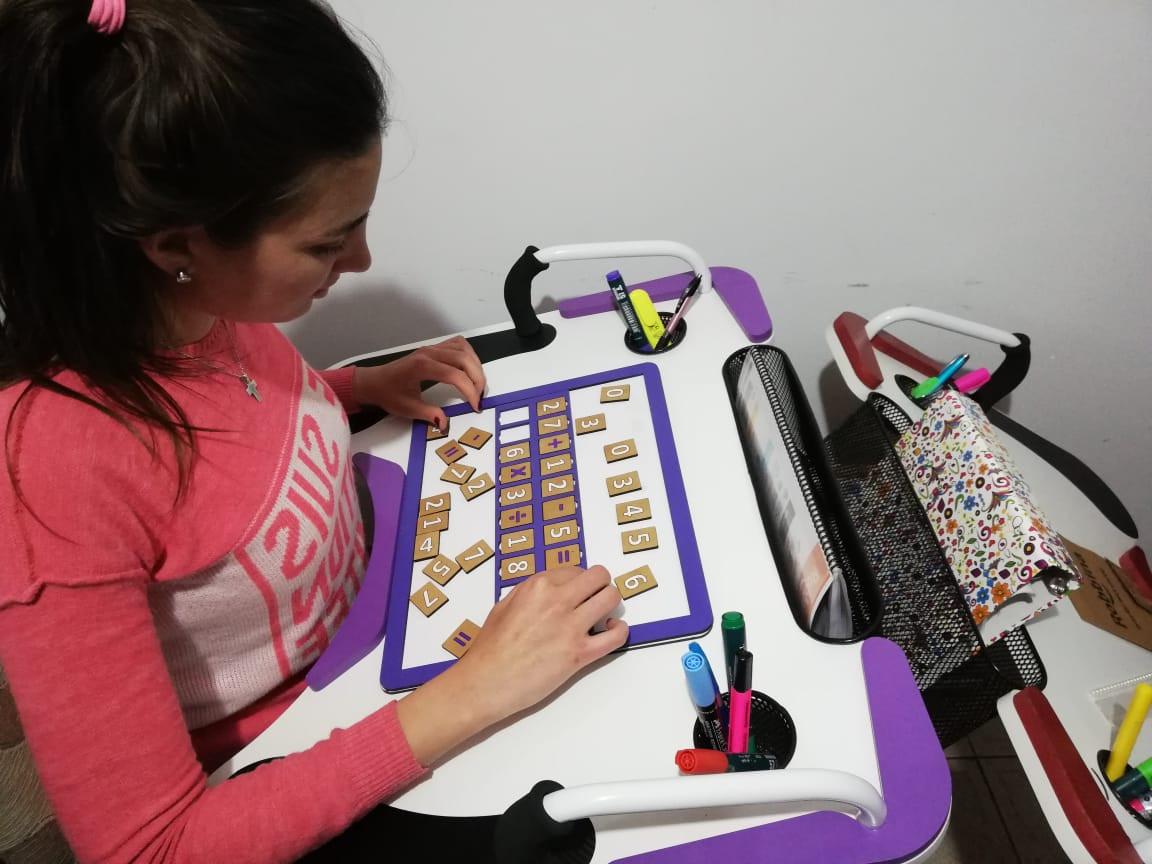 Chica utilizando fichas sobre la Mesa Inclusiva Robbina