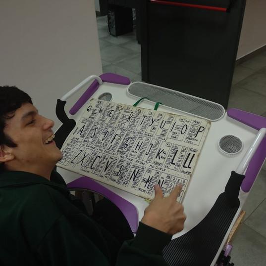 Chico utilizando tablero de comunicación sobre la Mesa Inclusiva Robbina