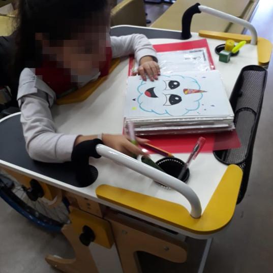 Niña en escuela usando un cuaderno sobre la Niña en escuela escribiendo y sujetándose desde la manija en la Mesa Inclusiva Robbina