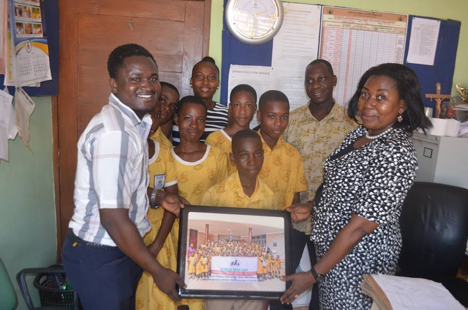 Christiana Achumboro and Peter Sampson accept a lamintated and framed group photo on behalf of the Cheetah KC