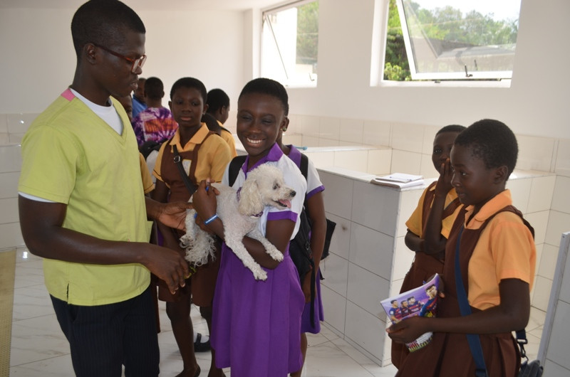 Her 1st experience holding a poodle--poodles are not common in Ghana!