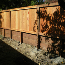 Redwood fence over a retaining wall