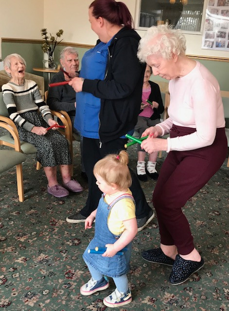 Toddler and older adult dancing