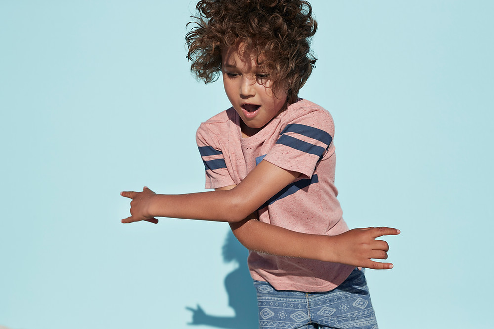 Young boy with long curly hair crosses arms as a dance move.