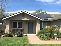 Tan home with landscaping and solar panels
