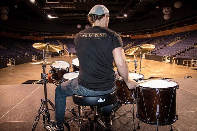 Samuel Welch on the stage of the 1st Bank Center with the Intuition drum tuning system