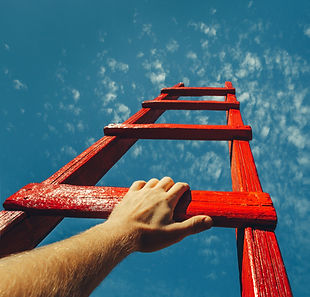 the hand and arm of a person climbing a ladder - a metaphor for leadership and self-leadership