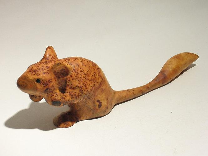 Une souris mouchetée avec une longue queue en forme de pinceau. Sculpture en bois de Christian Delacoux, 23 cm de longueur.