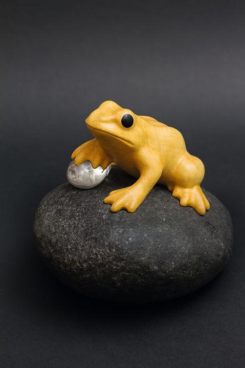 Grenouille jaune sur son galet qui coince une bulle d'eau avec sa patte. Sculpture en bois de Christian Delacoux, h 14 cm.